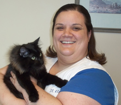 Team member Dr. Kristie Ellis holding a fluffy black cat